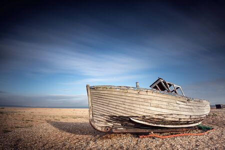 Single abandoned old fishing boat on a pebble beach with long exposure. Dungeness, England