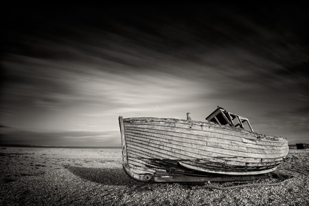 Singke abandoned old fishing boat on a pebble beach in monochrome. Dungeness, England Stock Photo
