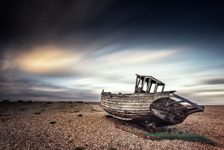 Singke abandoned old fishing boat on a pebble beach with long exposure clouds. Dungeness, England