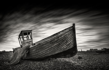 Single abandoned fishing boat on a pebble beach with long exposure clouds in monochrome. Dungeness, England