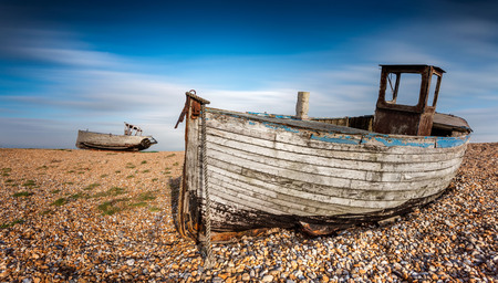 Old abandoned fishing boats on a pebble beach with long exposure clouds. Dungeness, England