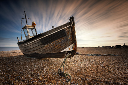 Single abandoned old fishing boat on a pebble beach with long exposure clouds. Dungeness, England Stock Photo