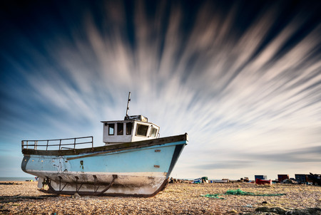 Abandoned old fishing boat on a pebble beach with long exposure clouds. Dungeness, England