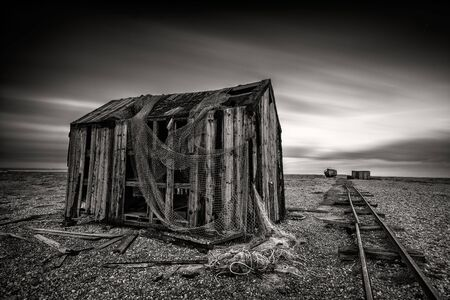 Abandoned fishermans hut on a pebble beach with long exposure clouds in monochrome. Dungeness, England