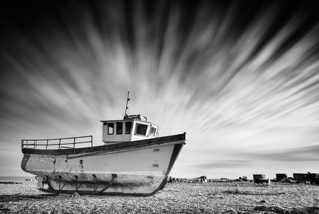 Abandoned old fishing boat on a pebble beach with long exposure clouds in monochrome. Dungeness, England