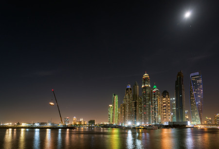 Night view of a moonlit Dubai Marina with reflections in the harbour.