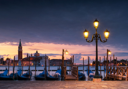 Long exposure view of gondolas by lamp light with San Giorgio church across the Grand Canal, Venice, Italy