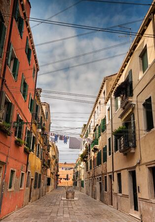 Narrow Venitian street with water wells and washing lines. Stock Photo