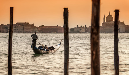 Romantic evening gondola journey for a couple on the Grand Canal. Venice, Italy