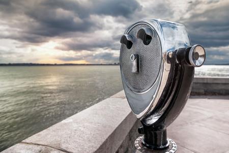 Binoculars on Ellis Island pointed towards Manhattan Island at dusk