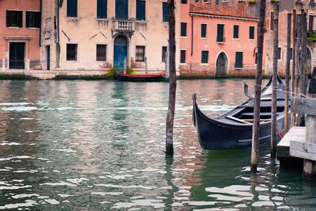 venice: Single gondola moored at a jetty on a canal in Venice, Italy