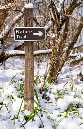 Nature trail sign on a hiking path in a snow covered forest Stock Photo - 97304166