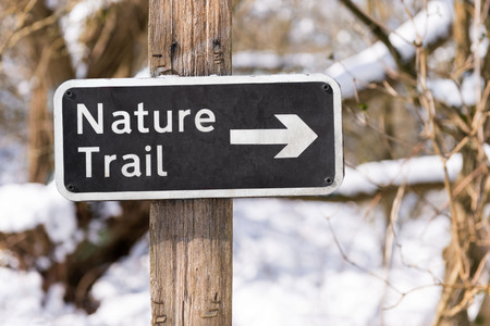 Nature trail sign on a hiking path in a snow covered forest Stock Photo - 97052357