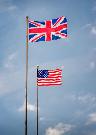 British and American flags on flagpoles with blue skies on a sunny day Stock Photo - 103052113