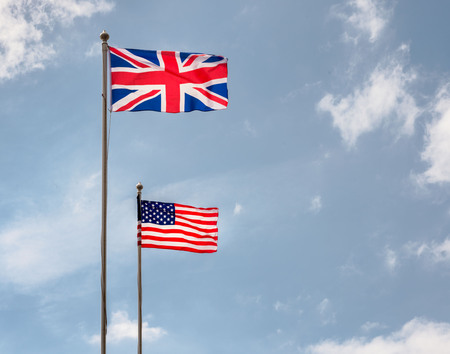 British and American flags flying on flagpoles with blue skies on a sunny day
