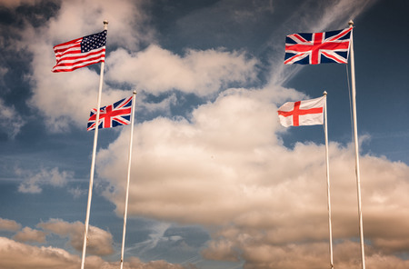 English, British and American flags on flagpoles with blue skies on a sunny day Stock Photo - 103097527