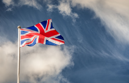 Union Jack flying in the wind on a flagpole with blue skies on a sunny day Imagens