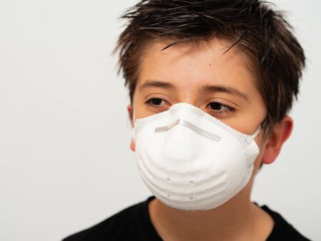 CHILD WITH BLACK T-SHIRT AND MASK READY TO GO OUT ON A WHITE BACKGROUND AND WITH COPY SPACE