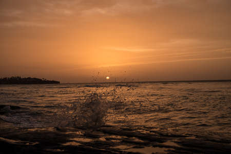 afterglow: Sunset at the beach with waves, afterglow and spray