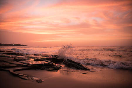 afterglow: Sunset at the beach with waves and afterglow