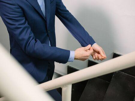 Man in blue blazer jacket walking upstairs while fixing sleeve