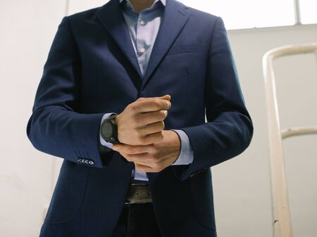 Man in blue blazer jacket with watch walking down stairs while fixing sleeve Banque d'images