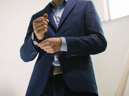 Man in blue blazer jacket with watch walking down stairs while fixing sleeve