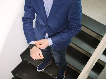 Man in blue blazer jacket with watch walking upstairs while fixing sleeve Banque d'images