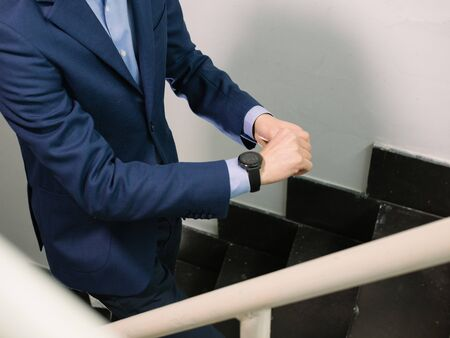 Man in blue blazer jacket walking upstairs checking the time on his watch