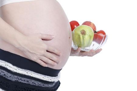 Pregnant woman with fresh fruit isolated over white background Stock Photo