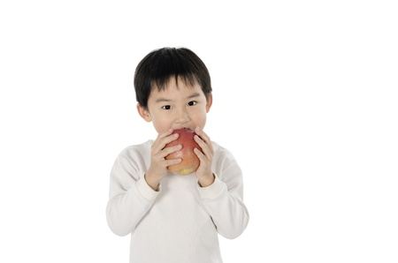 Cute little boy eating an apple with white background Stock Photo