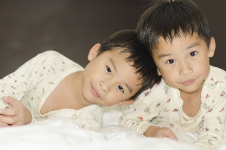 two twins brothers lying on bed Stock Photo