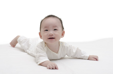 bedcover: Cute baby lying on white bedcover