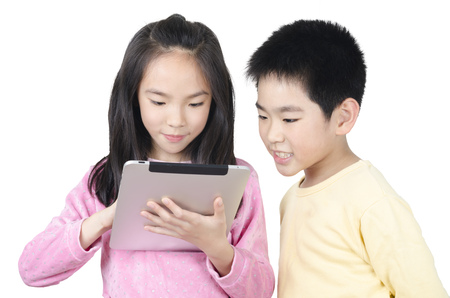 two happy children using touch pad computer and isolated on white