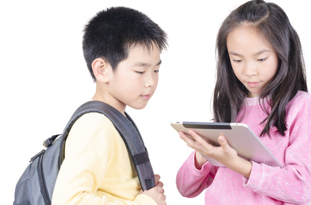 Smart children using touch pad computer and isolated on white