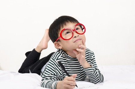 Smart child lying on bed  writing and thinking photo