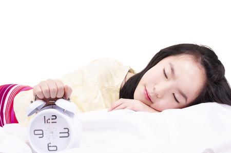 Sleeping girl with clock alarm Imagens