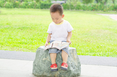 Boy enjoys reading book outdoor