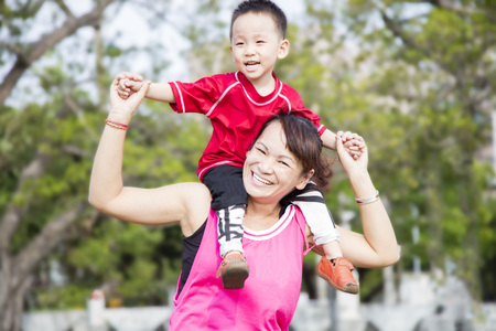 Happy cute boy on his mother shoulder