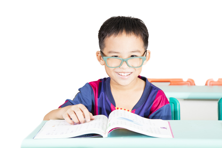 Smart kid reading book in classroom Stock Photo