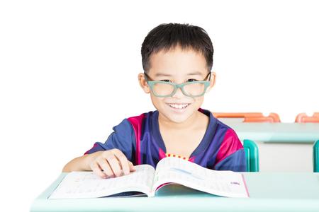 Smart kid reading book in classroom Stock Photo