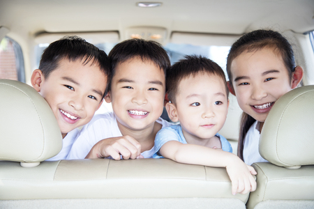 Happy children traveling by car