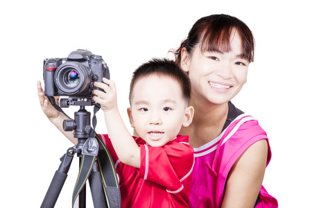 stool test: Smart kid with mother playing camera isolated background Stock Photo