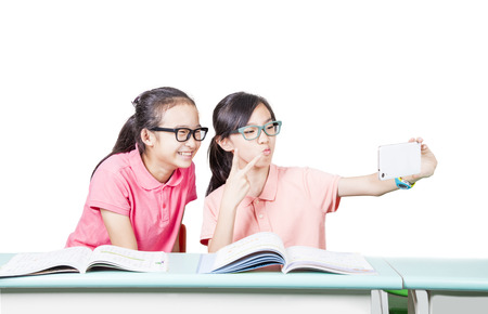 Girl students playing cellphone in the classroom Stock Photo