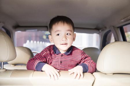 Cute boy traveling by car
