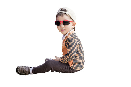 Cute kid wearing sunglasses and sitting on the ground Stock Photo