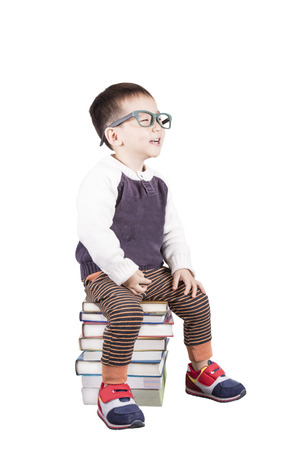 Adorable child studying with books and apple in the head a over white background.