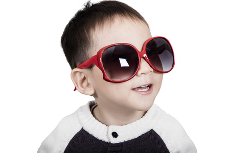 Cute kid is wearing sunglasses and smiling