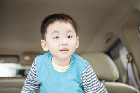 A little chinese boy standing in the back of car.
