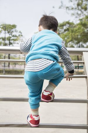 Brisk boy climbing at railing